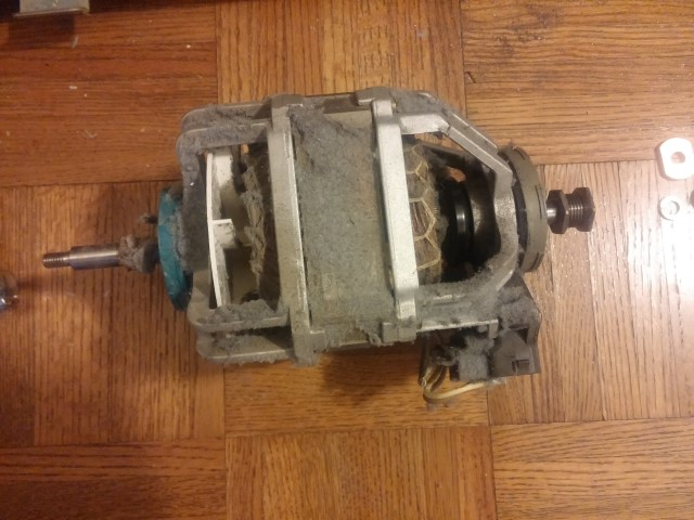 The old dryer motor, covered in dust, ready for recycling.