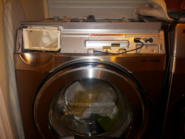 Front control panel removed from the front of washing machine.