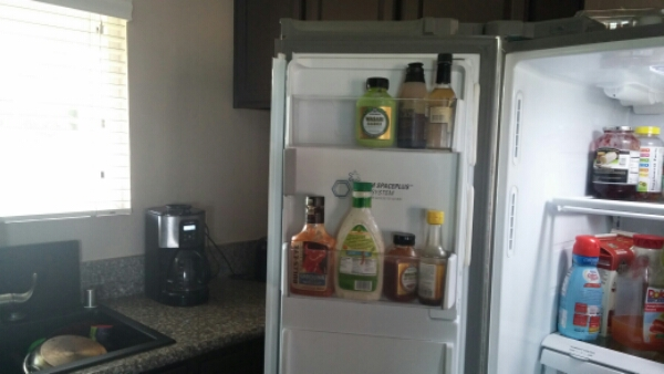 Removing various condiments and shelves from the refrigerator's door.